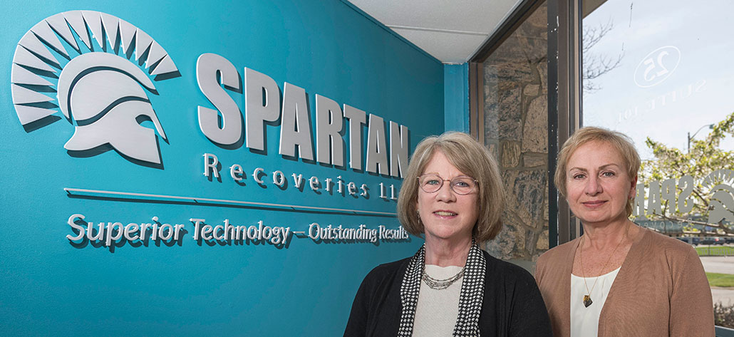 Kathy and Donna in front of the Spartan sign in the lobby.